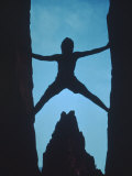 Silhouette of Rock Climber Between Two Rocks