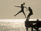 Silhouette of Girls Jumping off Pier