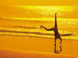 Girl Doing Cartwheels on Beach at Sunset