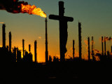 A Crucifix is Silhouetted against Refinery Stacks