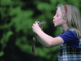 A Young Girl Plays Out a Fairy Tale as She Prepares to Kiss a Frog