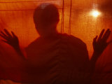 A Buddhist Monk is Silhouetted Behind a Hanging Curtain