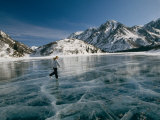 A Girl Ice Skates Across a Frozen Mountain Lake