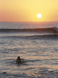 A Woman Paddles out to Sea for Sunset Surfing
