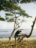A Woman Stretches Her Body on a Small Tree at a Sandy Beach