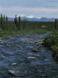 Mountain Stream with Cabin in Evergreen Forest in Distance