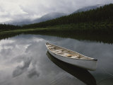 A Canoe Sits Tethered to Shore on a Beautiful Mountain Lake