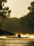 A Kayaker Paddles the River in a Morning Mist