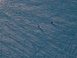 Aerial of Snowmobiles on a Frozen River Patterned with Tracks