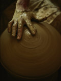Close-up of the Brown Muddy Hand of a Potter as He Spins a Clay Pot on His Wheel