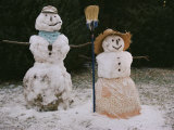 A Pair of Cheerful Snow-People Dressed with Hats  Scarf  Apron  and Broom