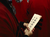 Buddhist Priest Holds Prayer Cards in his Hands