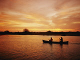 A Couple Rowing a Canoe is Silhouetted against a Gorgeous Sunset