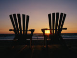 Two Chairs on a Shoreline Facing the Setting Sun