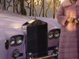 A Woman Wearing a Pink Mink Coat Stands Next to a Pink Rolls Royce