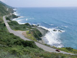 A Car Whizzes Down Hwy 1 Along Californias Big Sur Coastline