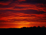 A Sunrise Bathes the Clouds in a Red Glow