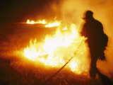 Fire-Fighter Silhouetted against the Flames of a Grass Fire