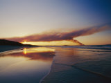 Smoke from a Brushfire Forms a Large Cloud over a Shoreline Bathed in Low Sunlight