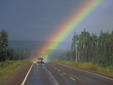 A Car on a Highway Drives Close to a Rainbow