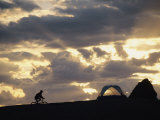 A Mountain Biker Cycles Toward Tents at a Campsite