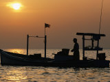 A Silhouetted Boat Fishing for Soft Crabs
