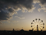 A Ferris Wheel is Silhouetted against the Evening Sky