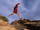 A Runner Leaps Across Rocks in Moab  Utah