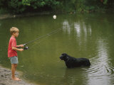 Boy Fishing in a Pond with a Black Labrador Retriever Standing in the Water