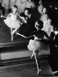 Ballet Teacher Advising Little Girl and Group of Dancers at Ballet Dancing School Look On