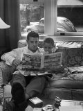 Father Sitting on Couch with Pigtailed Daughter Reading to Her the Sunday Comic Pages