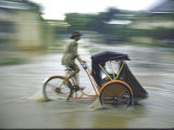 Man Driving Rickshaw During Monsoon Season