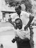 Italian Man Leaping Onto a Friend's Back in Casual Greeting While Crossing a Piazza
