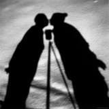 Shadows on Ground of Kissing Figures with Camera on Tripod Between