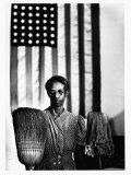 Ella Watson Standing with Broom and Mop in Front of American Flag  Part of Depression Era Survey