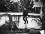 Man in a Suit and Bowler Hat Jumping in the Air in a Backyard in Brooklyn  Ny