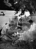 Friends Preparing Their Meal over a Camp Fire
