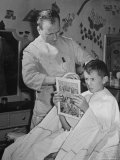 12 Year Old Boy Sitting in Barber Chair Having His Hair Cut and Reading Comics