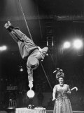 Circus Performer Balancer Unus Standing on His Index Finger on Globe Feet in Air Back of Head