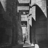 Man Walking Past Huge Carved Columns in Temple of Amon at Karnak in Thebes