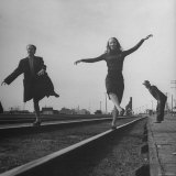 Two Young Ballet Russe Dancers Balancing on the Railroad Tracks in the Station While on Tour