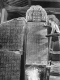 Man Standing on Ladder and Brushing Dust from Large Stone Tablets Covered with Writing