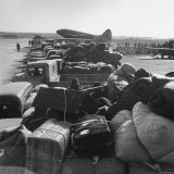 Airplanes Sitting on Airstrip at Airfield and Supplies Sitting in Trucks