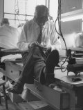 Custom Tailor Ernest Preedik Sitting on Table and Working in Factory