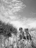 Children Sitting on a Sand Dune