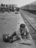 Aged Refugee Fighting Hunger  Sweeps Up Spilled Rice on the Railroad Station Platform