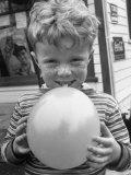 Little Boy Blowing Up a Balloon