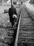 Elderly Hobo  with Bundle Strapped to His Back  Walking Along Train Tracks