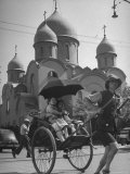 Family Being Pulled in a Rickshaw with a Russian Orthodox Church in the Background