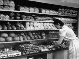 Good of Worker in Bakery Standing in Front of Shelves of Various Kinds of Breads and Rolls